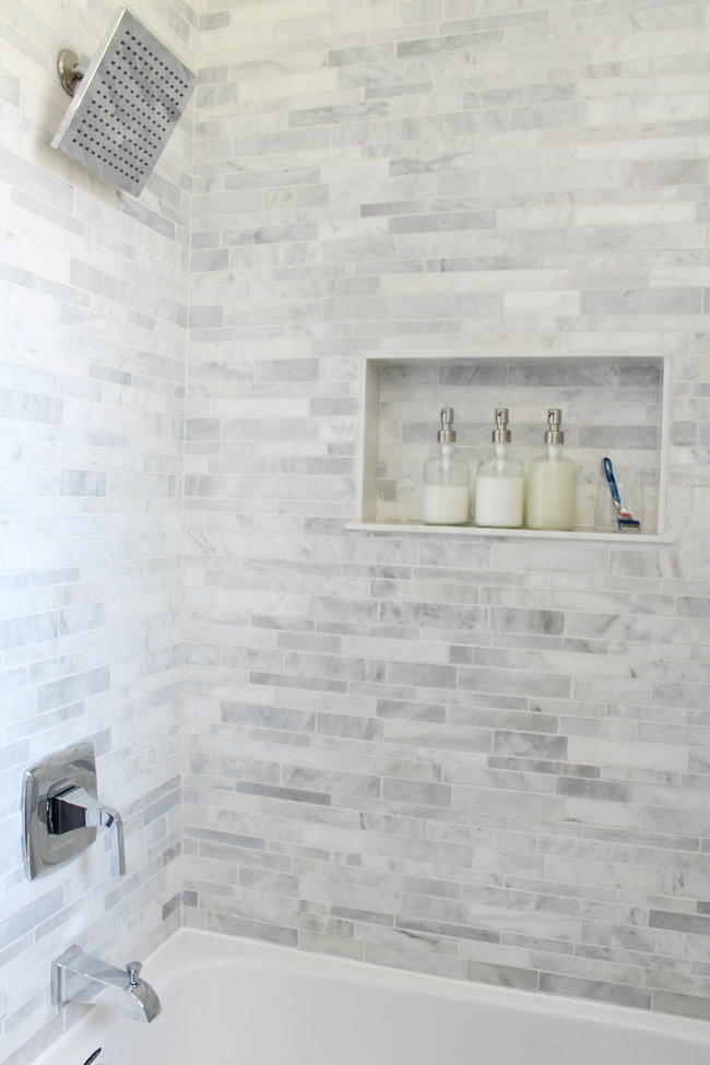 Bath and shower combo with mosaic marble tile with a storage niche.