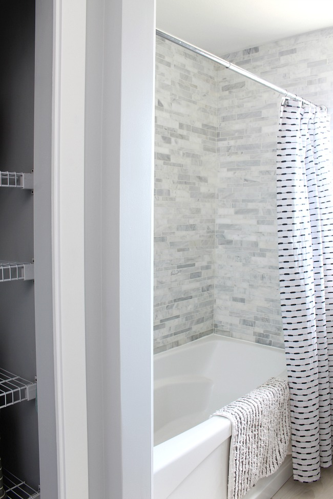 Bathroom makeover with a bath/shower combo with marble tiles.