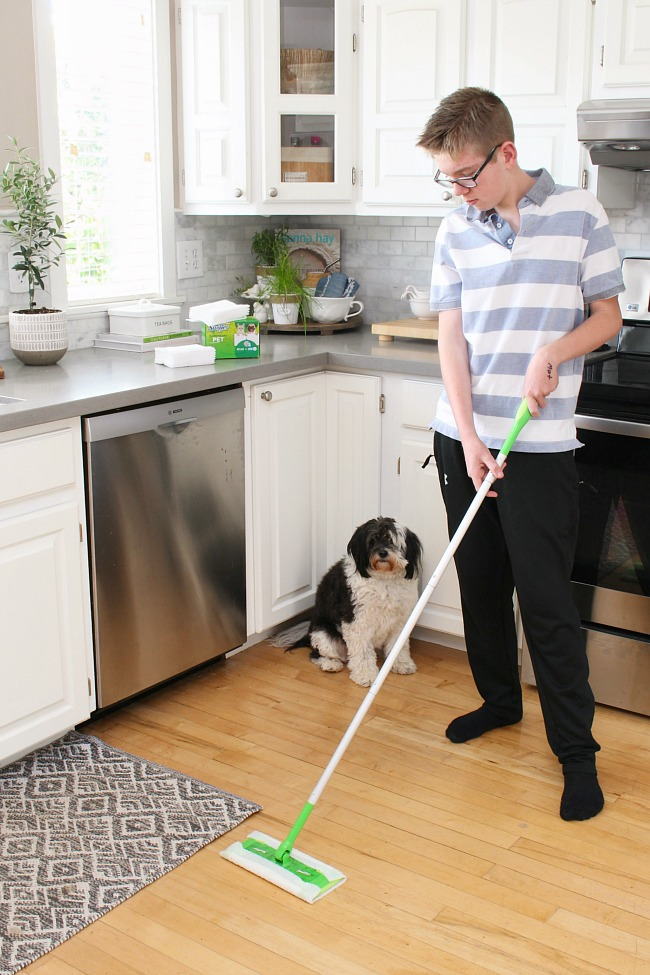 Teen using a Swiffer Sweeper on the kitchen floor.