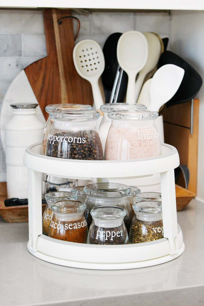 Spices in glass jars with vinyl labels on a lazy susan.