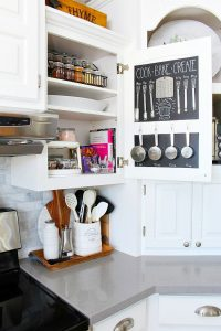 Organized cooking cupboard with chalkboard door and organized spices.