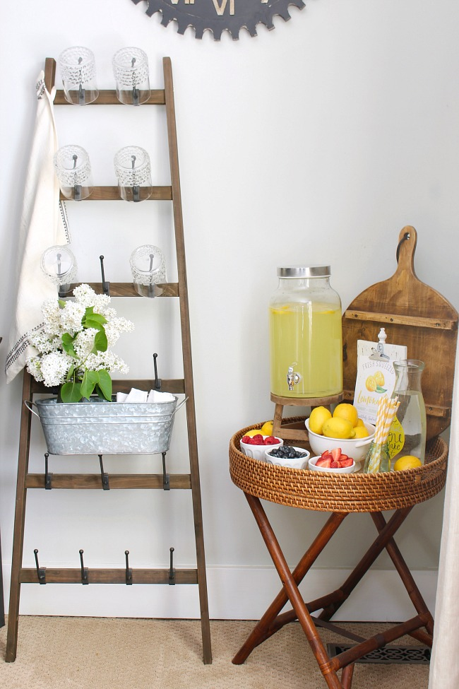 Rustic lemonade stand with wooden ladder rack and lemonade beverage station.
