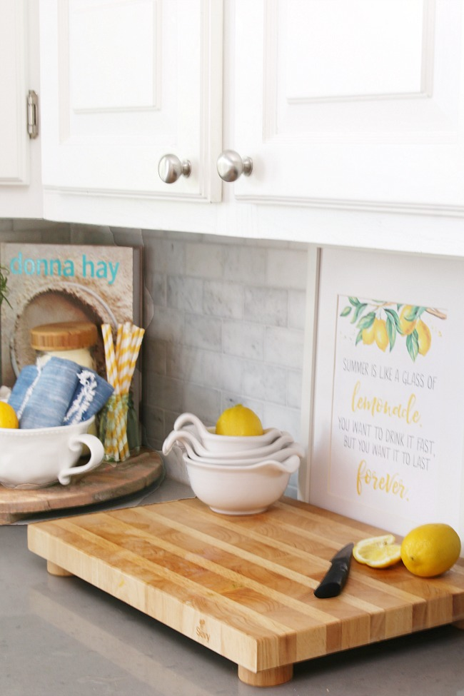 Free lemonade printable displayed in a picture frame in a white kitchen.