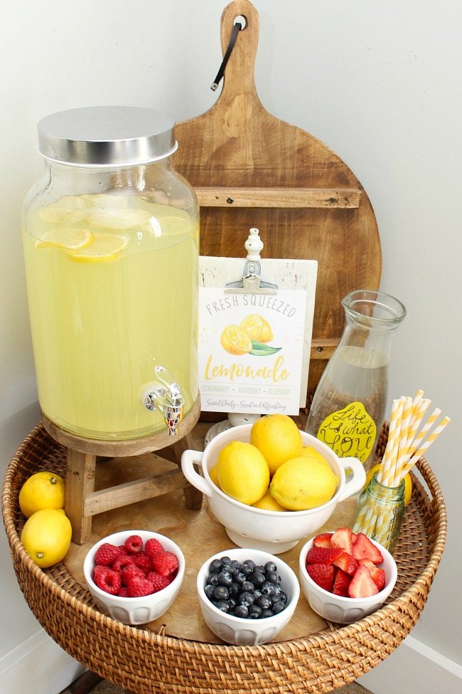 Lemonade bar with lemonade and fresh fruits. Free lemonade stand printables.