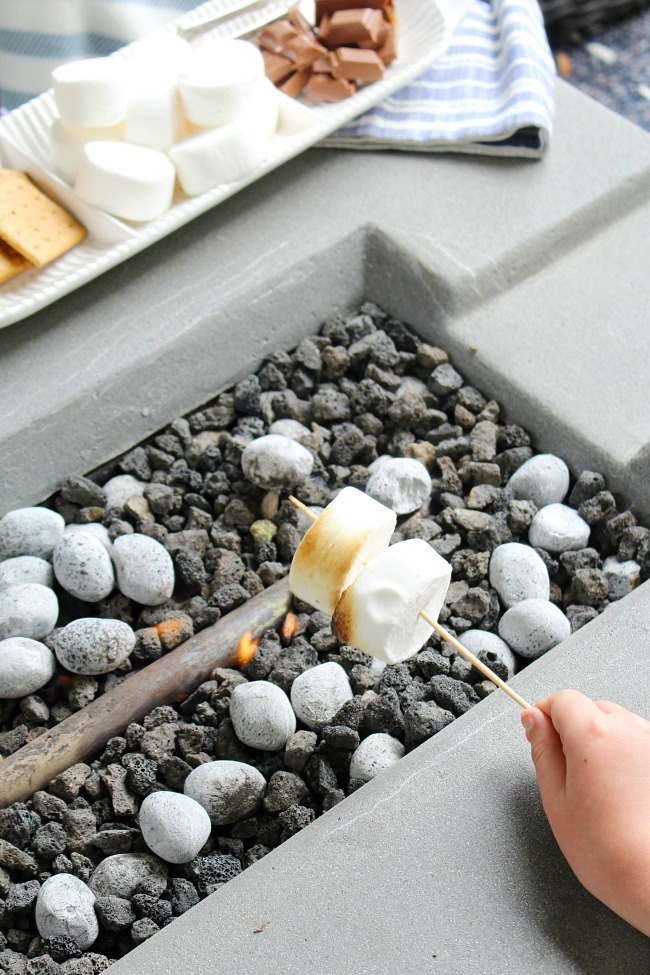 Roasting marshmallows for s'mores over a fire table.