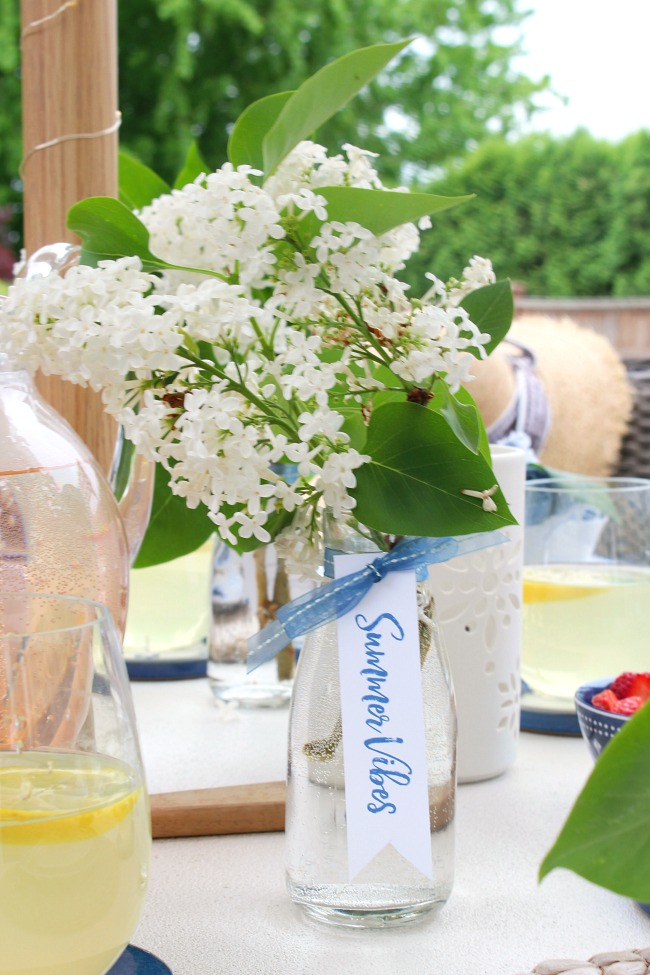 Simple glass bottle with white lilacs and decorated with ribbon and a free summer vibes printable. Perfect for simple summer entertaining!