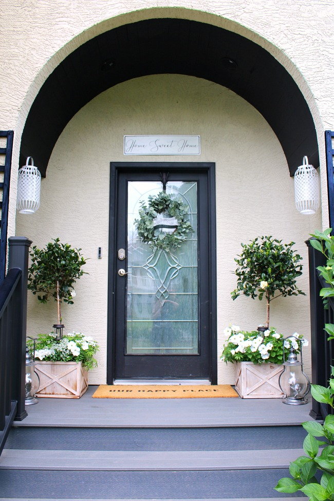 Traditional summer front porch with magnolia topiaries, white flowers and a black front door.