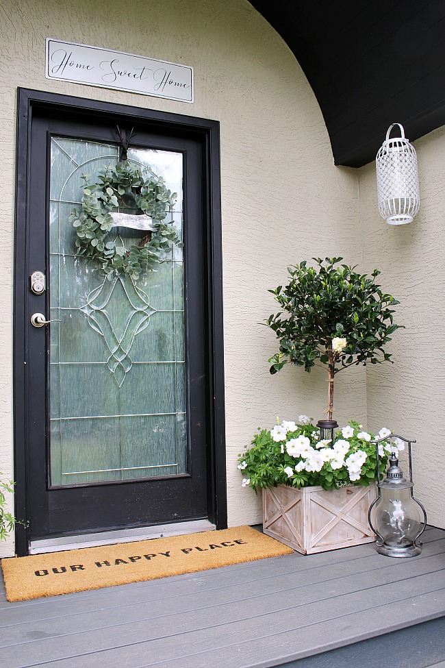 Pretty summer front porch decorated with magnolia topiaries, white flowers, and white and black accents.