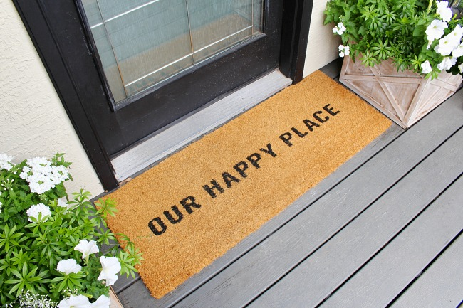 Our Happy Place front door mat on a traditional front porch.