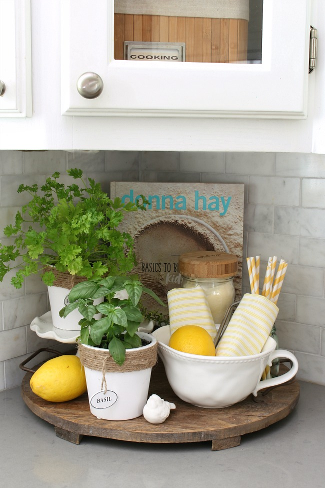 Summer vignette on a wood tray with lemons and herbs.