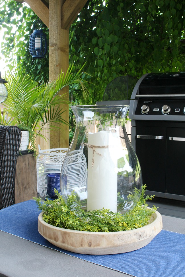 Outdoor centerpiece with hurricane glass, greenery, and an outdoor candle with timer.
