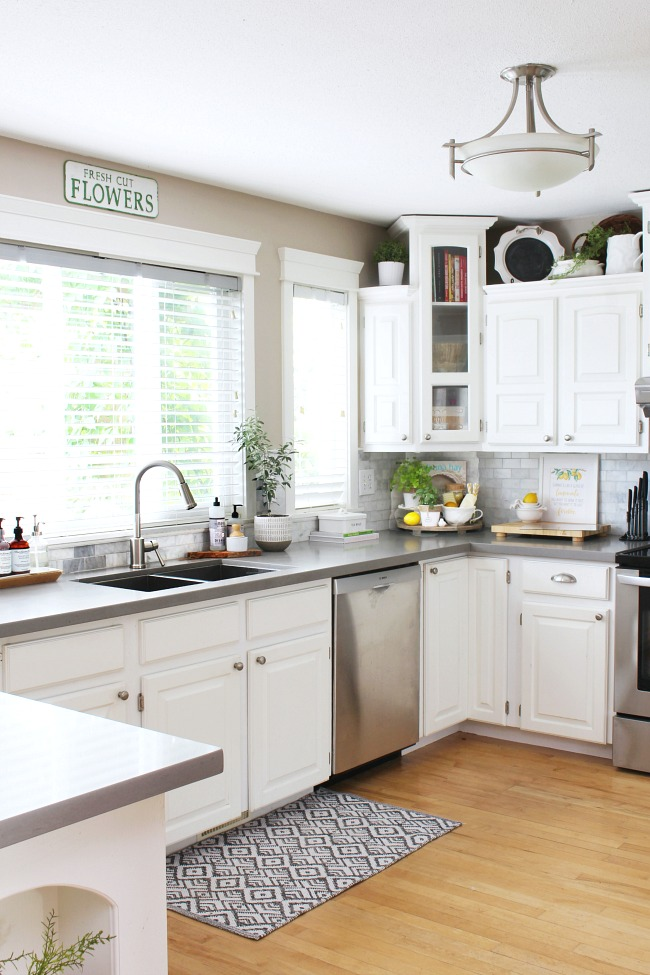 White farmhouse style kitchen decorated for summer with pops of lemon and some fresh greenery.