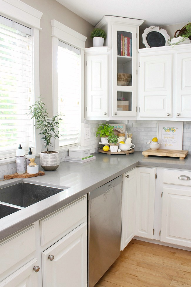 White farmhouse style kitchen decorated for summer with greens and yellow.
