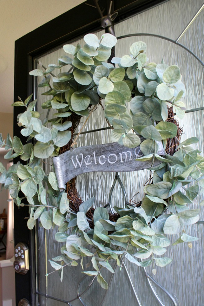 Eucalyptus wreath with a metal welcome sign hanging on a black front door.