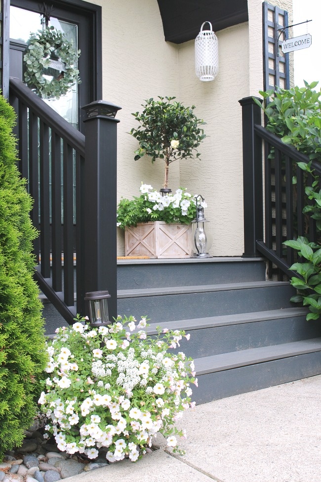 Traditional front porch with a various white flowers.