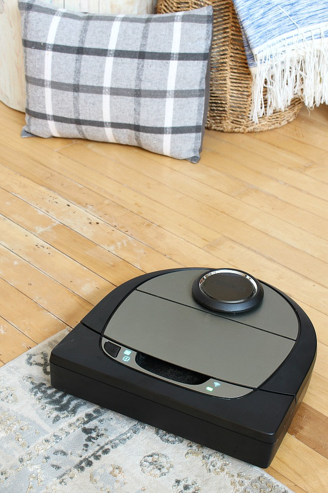 Neato D7 robotic vacuum on a hardwood floor and carpet.