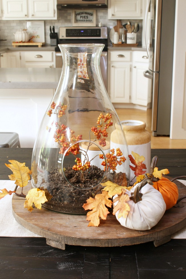 Fall centerpiece with a glass terrarium and fall leaves.