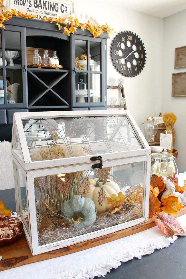 Pretty white terrarium with pumpkins and wheat for a beautiful DIY fall centerpiece.