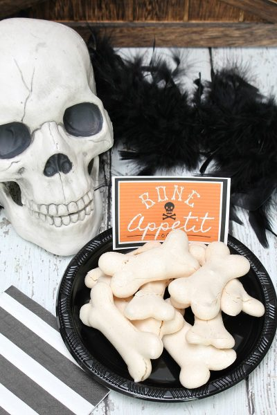 Meringue bones Halloween treats on a black plate with skull.