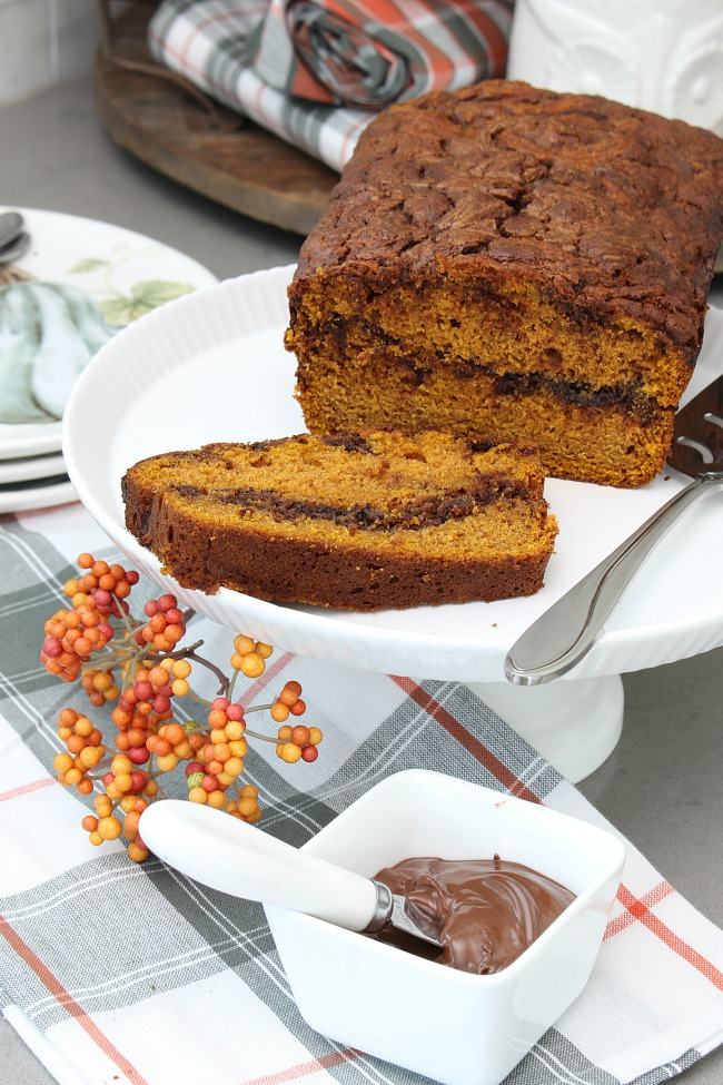 Pumpkin nutella swirl bread on a cake stand with white bowl of Nutella.