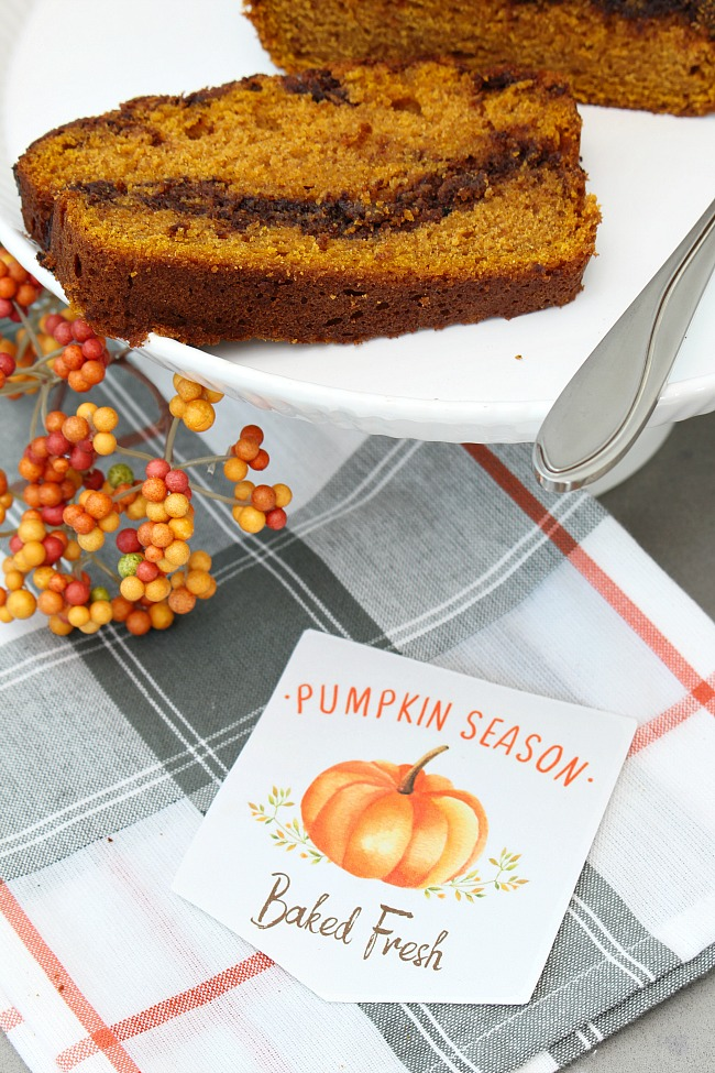 Nutella swirl pumpkin bread on a cake stand with a Baked Fresh fall printable baking tag.