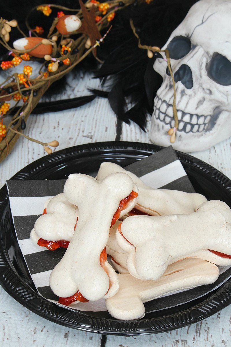 Meringue bones Halloween treats on a black plate with Bone Appetit printable.