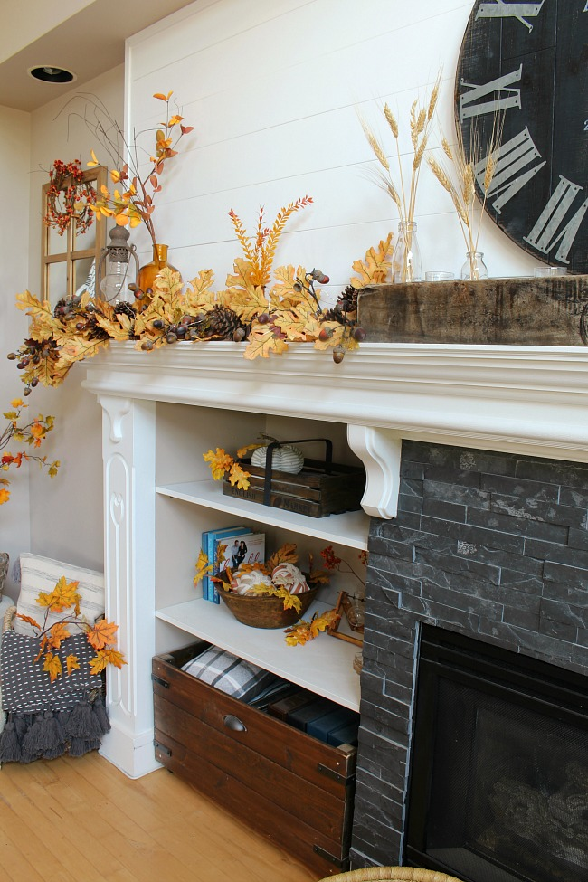 Beautiful shiplap fall mantel decorated with amber glass bottles and a golden oak leaf garland.