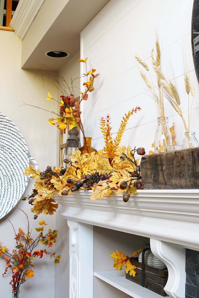 White shiplap mantel decorated for fall with amber and golden tones.