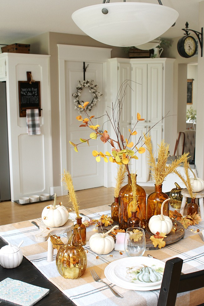 Fall or Thanksgiving tablescape using amber glass, golden tones, white pumpkins, and twinkle lights.