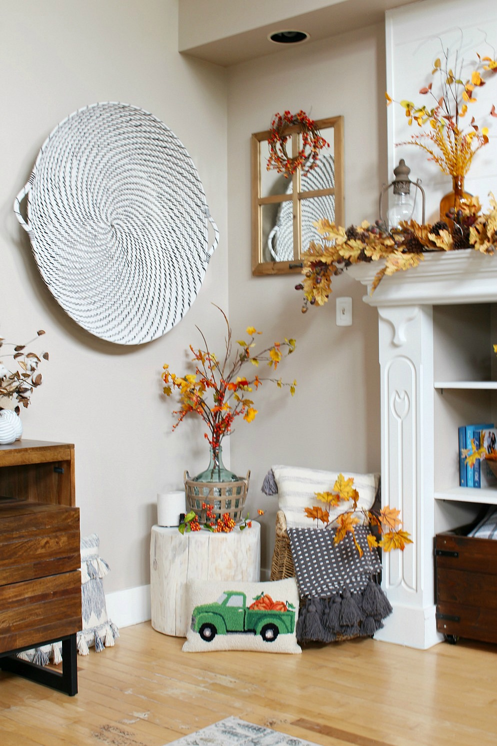 Fall family room decorated for fall with fall blankets, pillows, and faux fall branches.