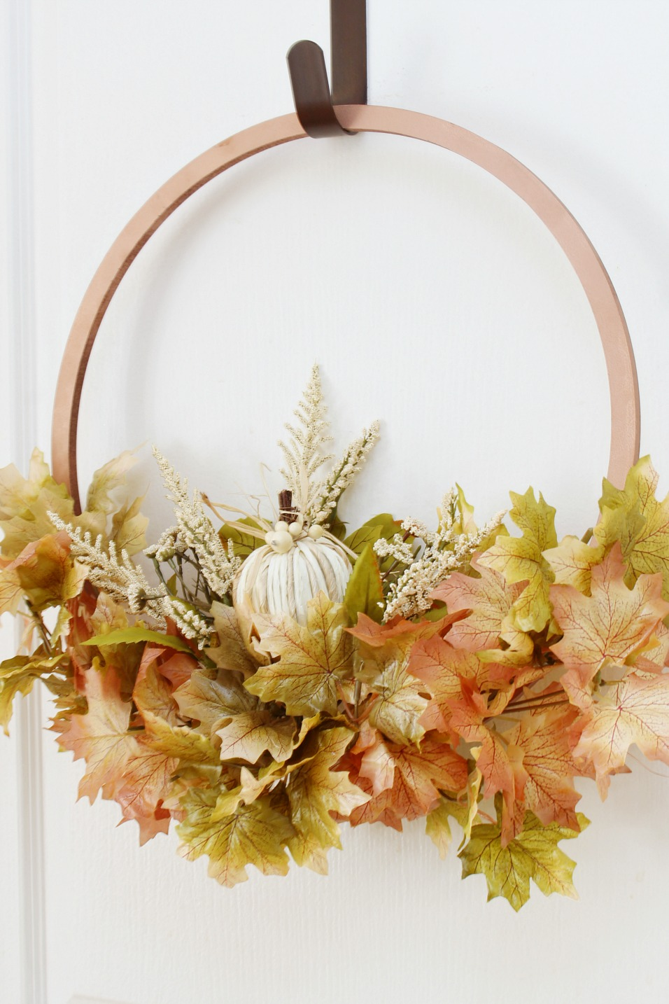 Copper hoop wreath with fall leaves.