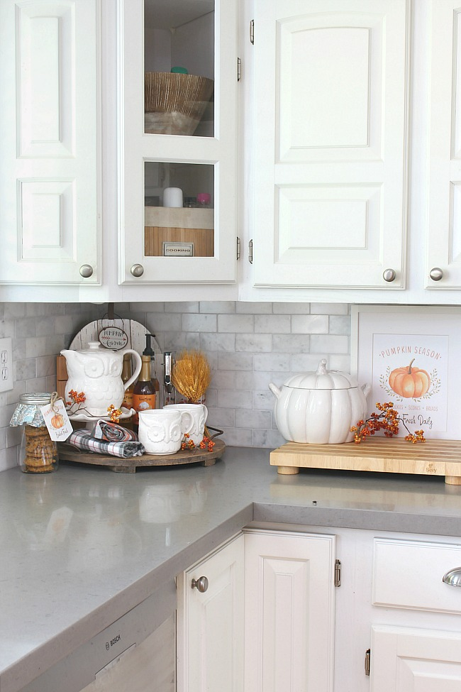 White farmhouse style kitchen decorated for fall with muted orange.