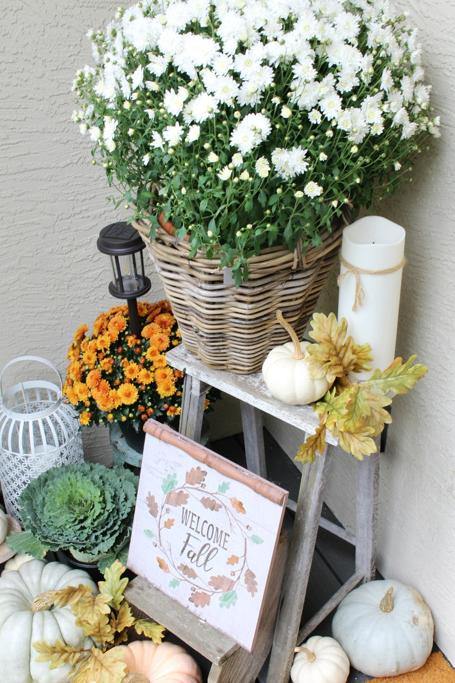 Fall front porch with mums and pumpkins on a vintage wood ladder.
