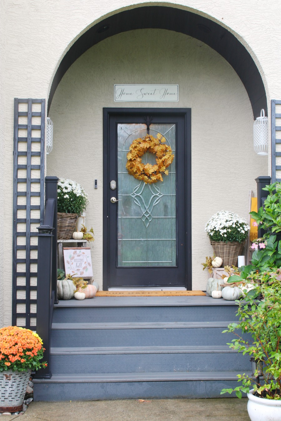 Farmhouse style fall front porch with mums and pumpkins.