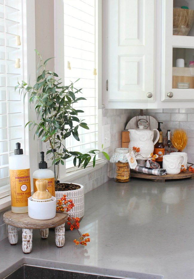 Farmhouse style white kitchen decorated for fall with simple touches and pops of orange.