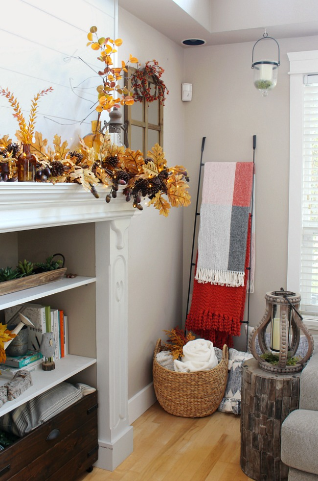 White mantel decorated for fall with a blanket ladder filled with cozy fall throw blankets.