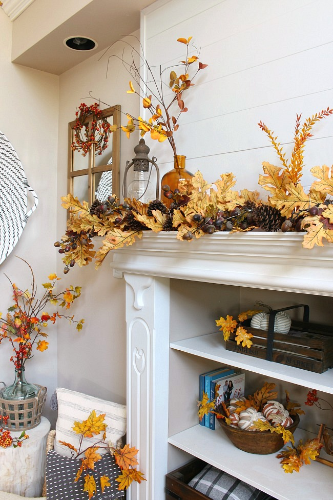Farmhouse style white mantel decorated with amber glass and a pretty oak leaf garland.