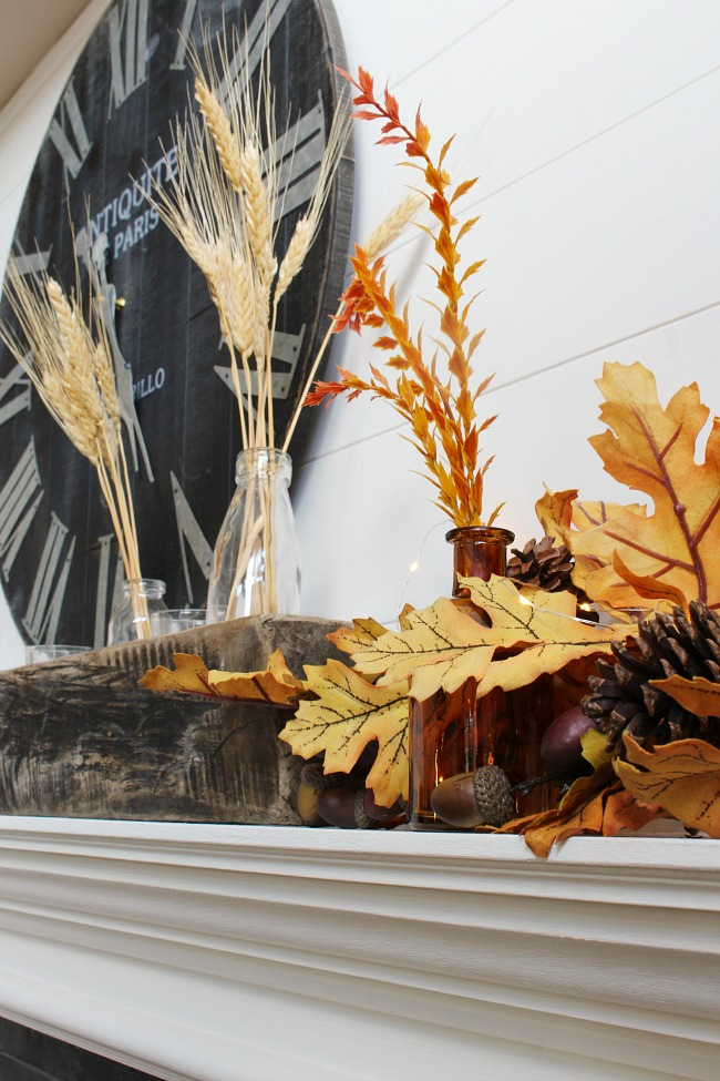 Fall mantel with wheat, wood, amber glass, and golden oak leaves.