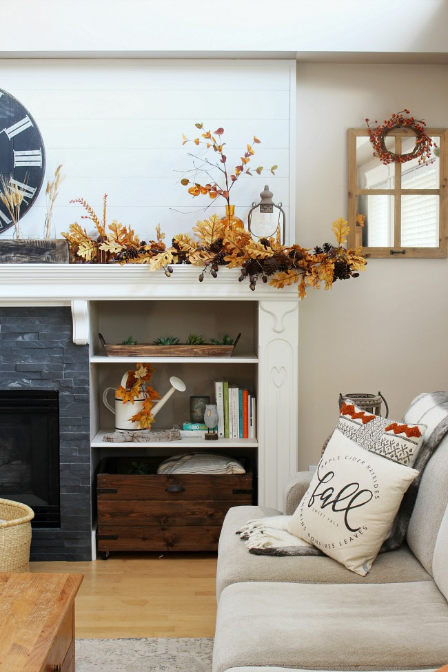 White farmhouse style mantel decorated for fall with amber glass and golden oak leaves.