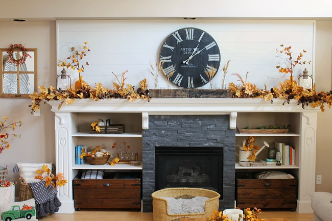 White shiplap mantel decorated for fall with amber glass and golden oak leaf garlands.