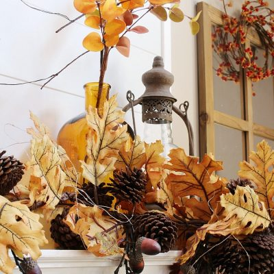 Beautiful amber glass bottles and golden fall stems create a beautiful fall mantel.