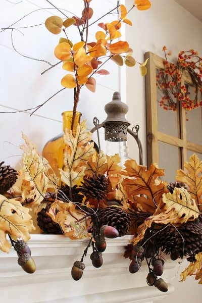 Beautiful amber glass bottles and golden fall stems create a beautiful fall mantel.