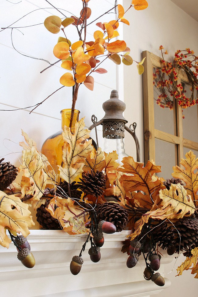 Beautiful amber glass with fall stems and golden oak leaves for a fall mantel.