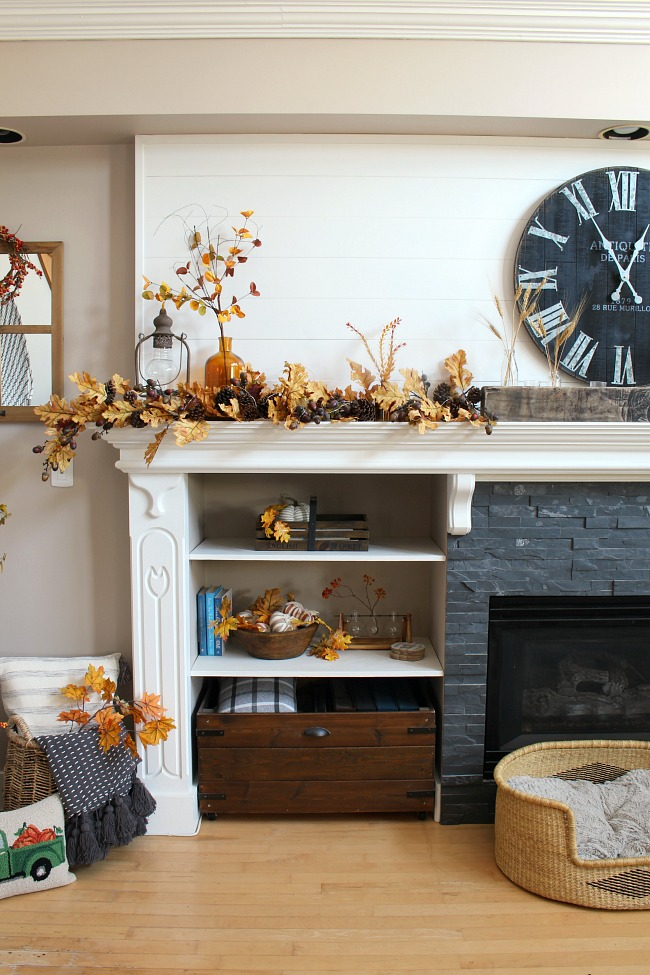 White mantel decorated with amber glass and golden oak leaves.
