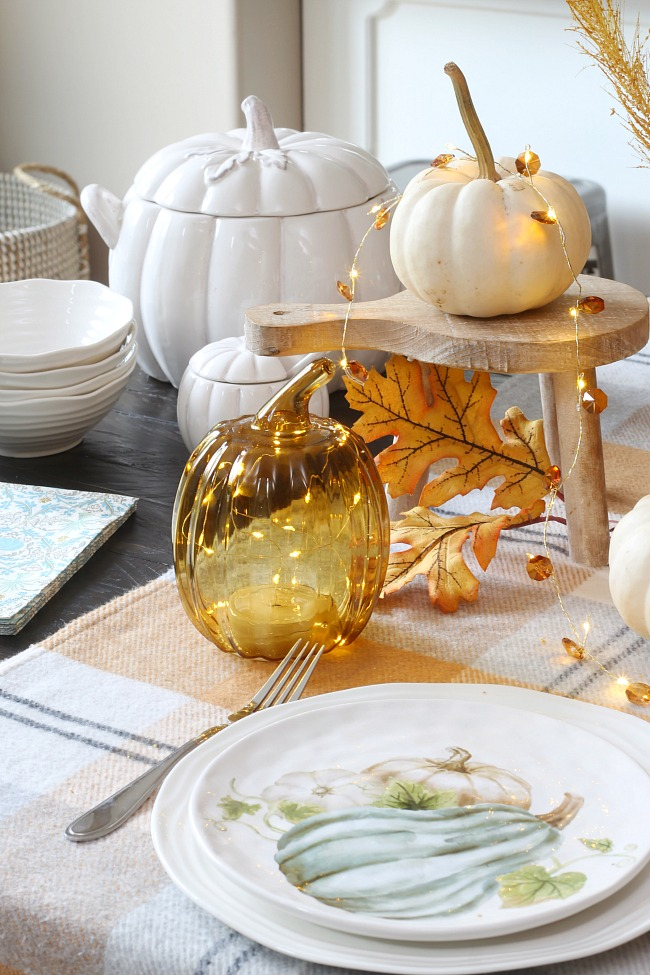 Fall place setting with mix of real and faux pumpkins with twinkle lights.