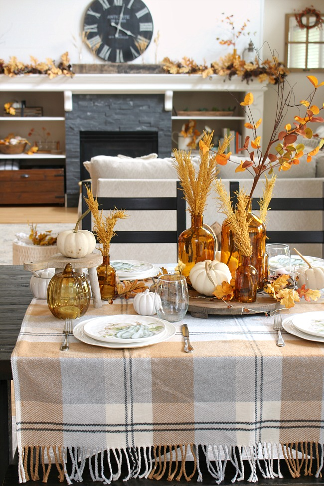 Harvest moon fall tablescape ideas using amber glass, white pumpkins, and muted fall colors.