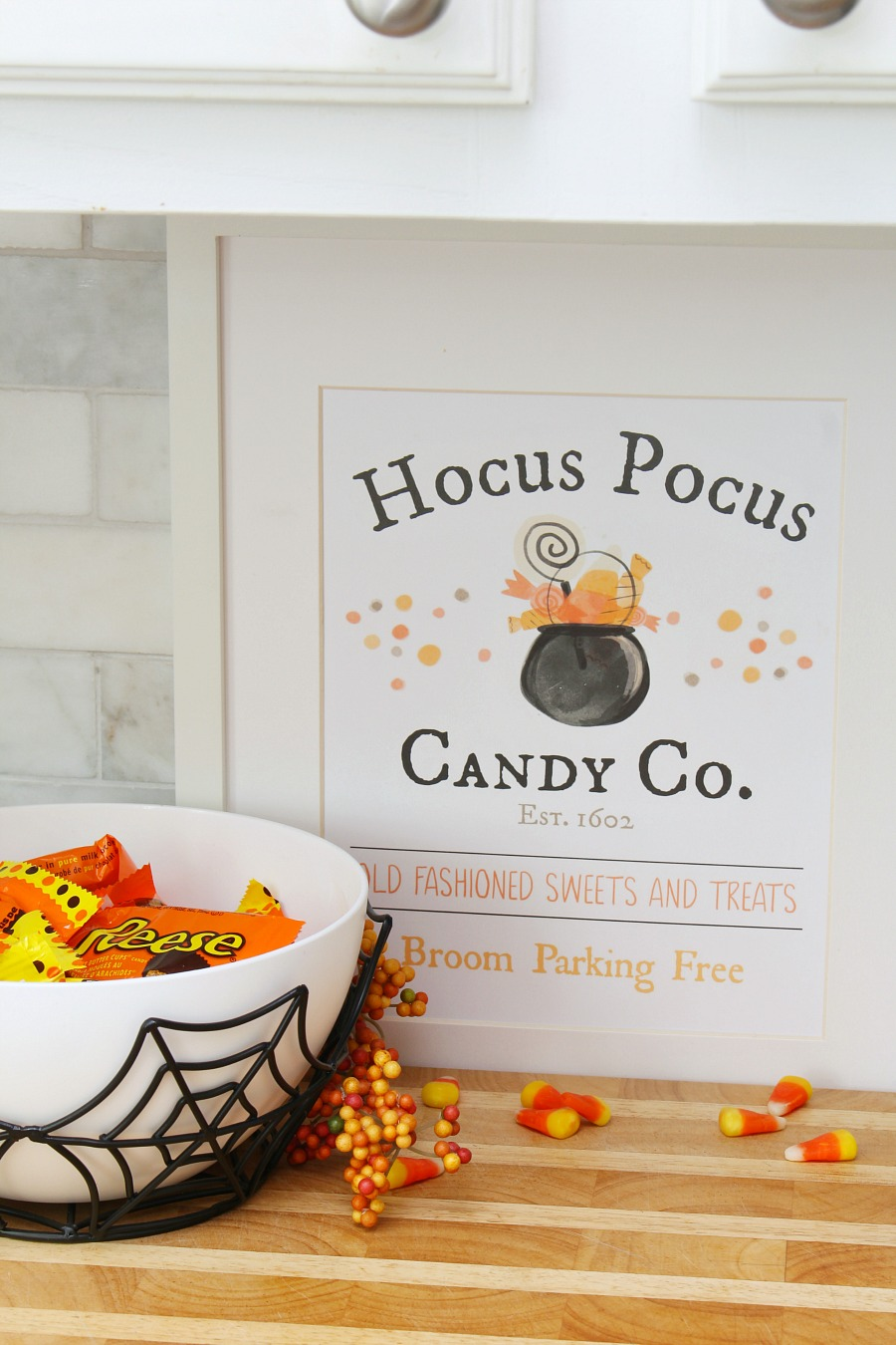 Hocus Pocus Candy Co. free Halloween printable displayed in a frame beside a Halloween candy bowl.