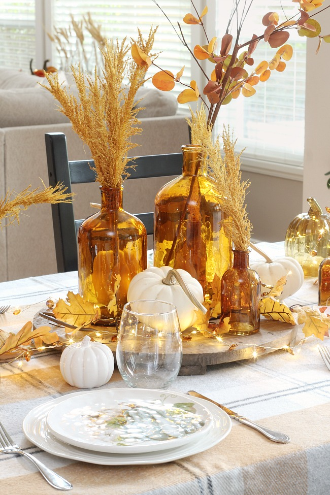 Pretty fall tablescape ideas using amber glass for a centerpiece and fall plates.