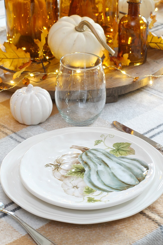 Pretty fall or Thanksgiving place setting with fall salad plate, amber glass, pumpkins and twinkle lights.