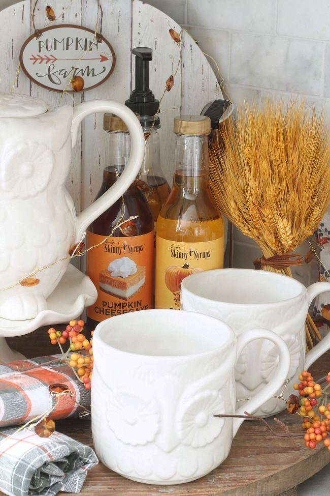 Cute fall beverage bar with white owl mugs and fall-flavored syrups.